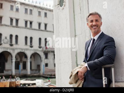 Porträt von lächelnden Geschäftsmann mit Koffer in Venedig - Stockfoto