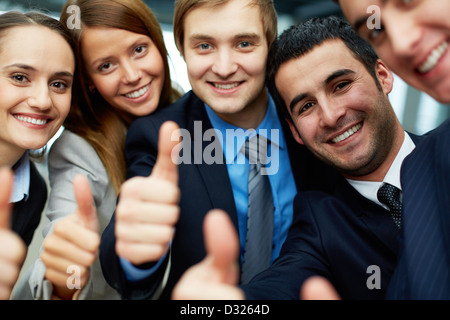 Porträt von fünf Geschäftspartner Daumen halten und mit einem Lächeln in die Kamera schauen - Stockfoto