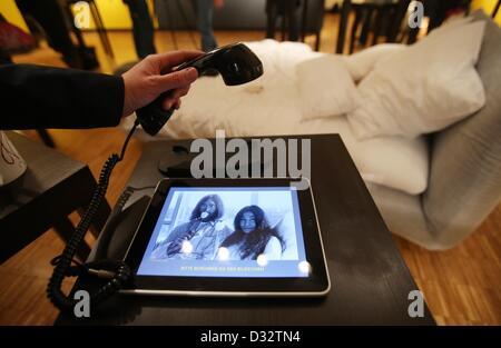 """Lübeck, Deutschland. 7. Februar 2013. Eine Frau schaut Foto von John Lennon und Yoko Ono während """"Bed In"""" auf einem - Stockfoto"""