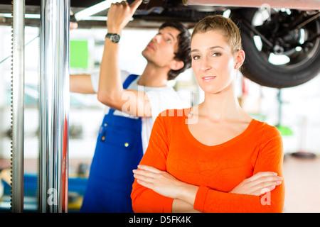 Frau stand vor ihrem Auto, das auf einem Auto Hebebühne steht, macht eine Reparatur unter dem Auto Mechaniker aufgehoben - Stockfoto
