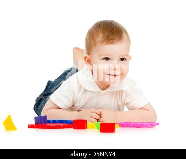 Nettes kleines Kind spielt mit Spielzeug auf Boden, liegend, isoliert auf weiß - Stockfoto