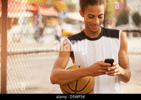 Mann mit Handy am Basketballplatz - Stockfoto