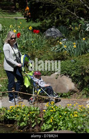 Eine weiße Mutter schiebt ihr Kleinkind in einem Kinderwagen an der Brooklyn Botanic Garden, New York, NY - Stockfoto