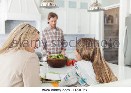 Mutter Tochter bei den Hausaufgaben zu helfen, während Vater Essen zu Kücheninsel bereitet - Stockfoto