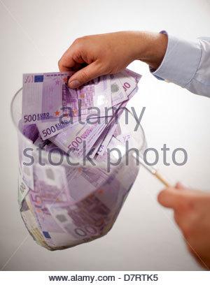 Nahaufnahme eines Mannes mit einem Fischernetz gefüllt mit 500 Euro-Banknoten - Stockfoto