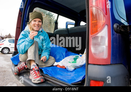Eine skandinavische Frau mit einem Snack im Kofferraum, Frankreich. - Stockfoto