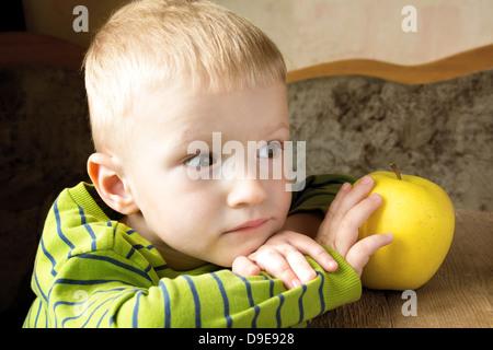 Kinder träumen und denken zu Hause mit gelber Apfel, Nahaufnahme Portrait mit Textfreiraum. - Stockfoto