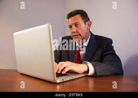 Ausgereifte Business-Mann an einem Schreibtisch mit einem Laptopcomputer. - Stockfoto