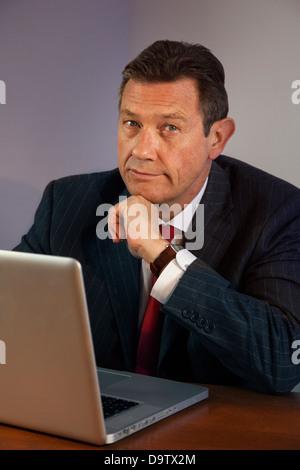Porträt-Business-Mann an einem Schreibtisch mit Laptop, Kamera suchen. - Stockfoto