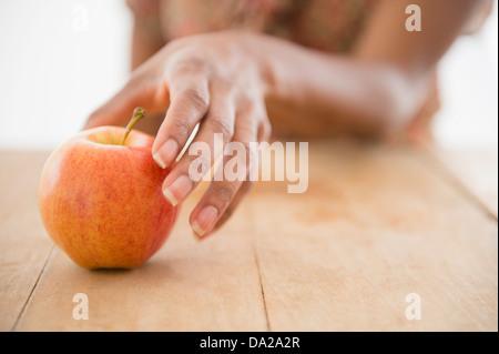 Zarte Frauenhand erreichen für apple - Stockfoto