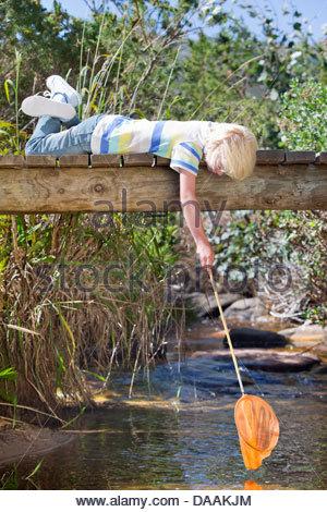 Junge am Steg und Dippen Fischernetz im stream - Stockfoto