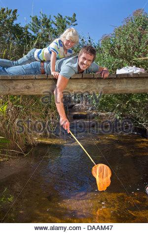 Porträt von lächelnden Vater und Sohn Verlegung auf Steg und Dippen Fischernetz im stream - Stockfoto