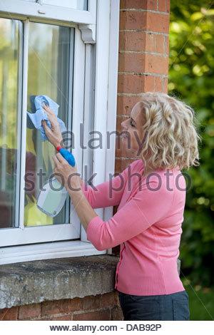 Eine reife Frau, die Reinigung von Fenstern eines Hauses - Stockfoto