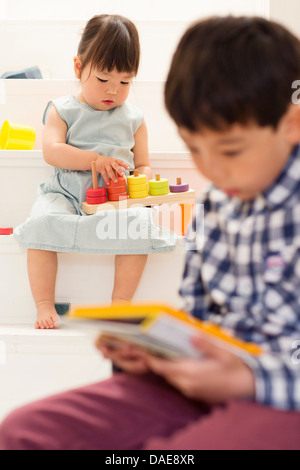 Bruder und Schwester spielt mit Spielzeug auf Treppe - Stockfoto
