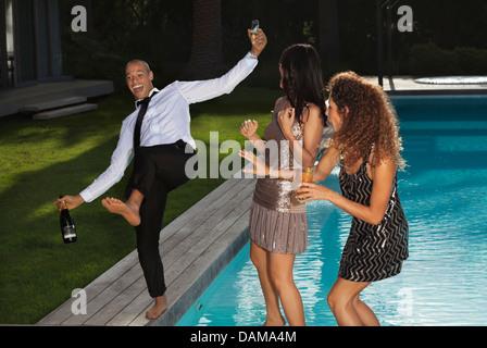 Freunde spielen am Swimmingpool - Stockfoto