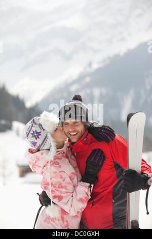 Brautpaar mit Skiern in schneebedeckten Feld küssen - Stockfoto