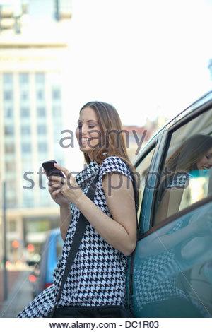 Junge Frau mit Handy Auto gelehnt - Stockfoto