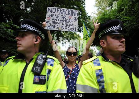 Balcombe, West Sussex, UK. 18. August 2013.  Eine junge Frau hält ein Plakat hinter Polizei Linie als Tausende von - Stockfoto