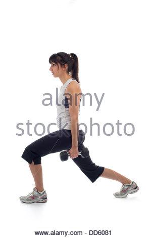 Junge Frau in einem schwarzen und weißen Übung Outfit Training mit Gewichten auf weißem Hintergrund. Sie ist im - Stockfoto