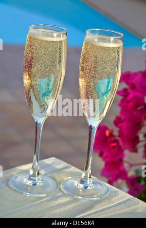Zwei Gläser Champagner auf sonnenbeschienenen Terrasse im freien Tisch Swimmingpool mit Bougainvillea Blumen frisch - Stockfoto