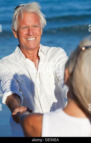 Glücklich senior Mann und Frau zu zweit tanzen und halten die Hände auf einem einsamen tropischen Strand mit blaue - Stockfoto