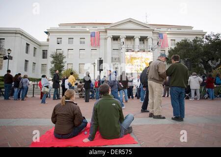 Ein paar sitzen auf einer Decke, die darauf warten, sehen Sie der Amtseinführung von Barack Obama am Großbildschirm - Stockfoto