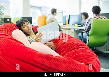 Geschäftsfrau mit Laptop in Bohnenbeutelstuhl im Büro - Stockfoto