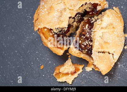 Eine gebrochene süße Weihnachten Hackfleisch Torte auf einer Tafel Kühlung Board. - Stockfoto