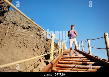 junger Mann trekking auf Holztreppen auf einem felsigen Pfad - Stockfoto
