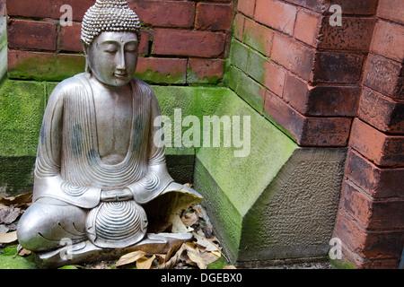Gebrochene Metall Buddha-Statue sitzt in einer Moss überdachte Ecke einer gemauerten Wand. - Stockfoto