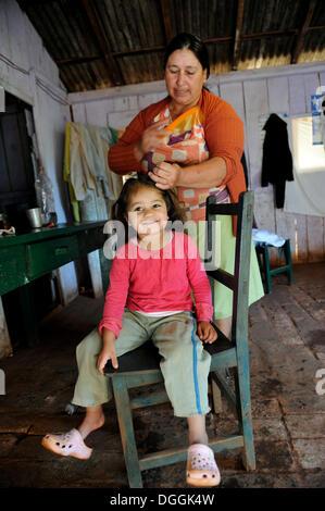Großmutter, 74, kämmen das Haar ihrer Enkelin, 3, Pastoreo, Caaguazu Abteilung, Paraguay - Stockfoto