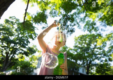 Ein junges Mädchen bläst Seifenblasen in der Luft unter den Ästen eines großen Baumes. - Stockfoto