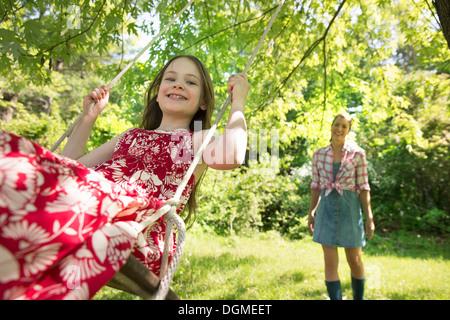 Sommer. Ein Mädchen in einem Sommerkleid auf einer Schaukel unter einem grünen Baum. Eine Frau, die hinter ihr stehen. - Stockfoto