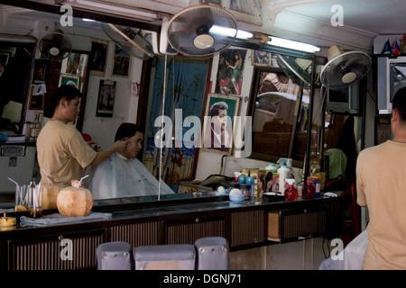 Ein Friseur gibt einem Mann einen Haarschnitt an Kennedy Frisörsalon in Phnom Penh, Kambodscha. - Stockfoto