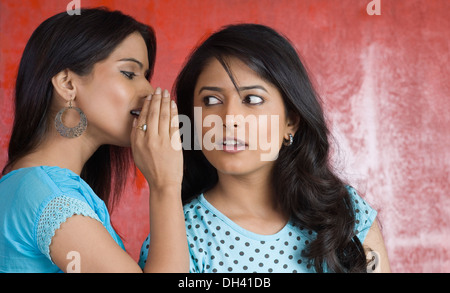Teenager-Mädchen zu einer jungen Frau Flüstern - Stockfoto