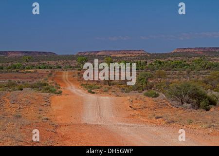 Australische Outback-Landschaft mit langen roten Piste Kreuzung Ebenen bis hin zu weit entfernten Bereiche am Horizont - Stockfoto