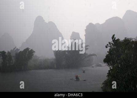 Boote auf dem Fluss an einem regnerischen Tag; Yangshuo, China - Stockfoto