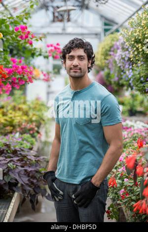 Ein junger Mann arbeitet in einem Gewächshaus voller blühender Pflanzen. - Stockfoto