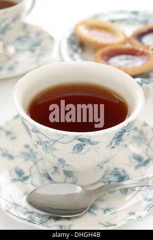Der Tee serviert in einem reich verzierten Teeservice schwarz - Stockfoto