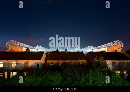 Old Trafford Stadion, Heimstadion von Manchester United, beleuchtet durch Flutlicht während einer klaren Himmel - Stockfoto