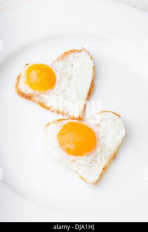 Herz Form Spiegeleier auf den weißen Teller - Stockfoto