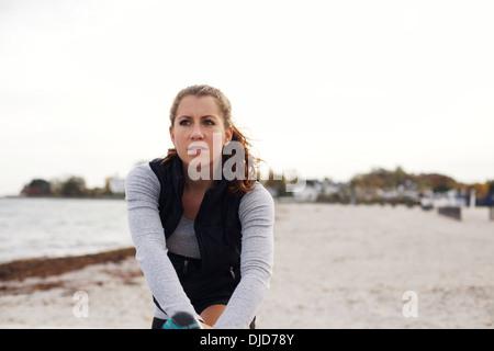 Attraktive Sportlerin in Sportbekleidung, ruhen Sie sich nach einem Training. Kaukasische Frau dehnen ihre Beine - Stockfoto