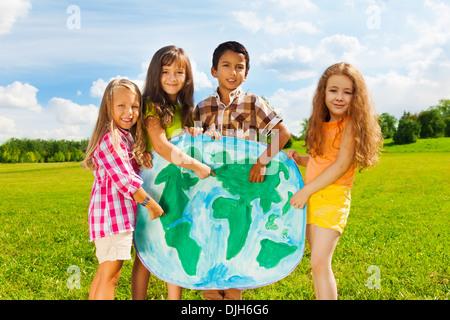 Gruppe von glückliche Kinder Jungen und Mädchen stehen und deutete auf die Globuskarte Darstellung Vielfalt Konzept - Stockfoto