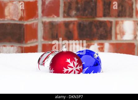 Rot, Silber und blau Christmas Ball ornaments auf Schnee, Ziegel Wand Hintergrund - Stockfoto