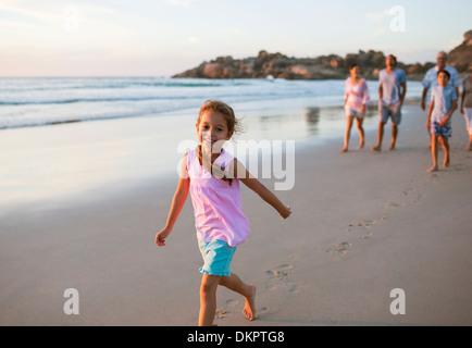 Mädchen zu Fuß am Strand mit der Familie im Hintergrund - Stockfoto
