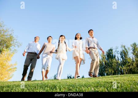 Glückliche Familie gehen Hand in Hand in einem park - Stockfoto