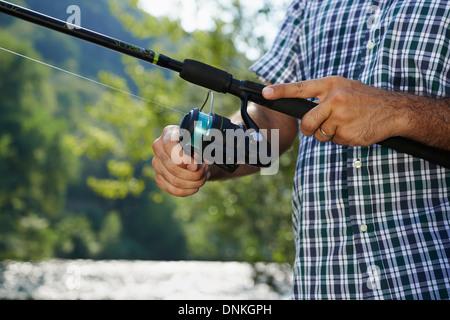 Nahaufnahme von Fisher am Fluss mit den Händen auf Walzen, relaxen und Angeln Forellen - Stockfoto