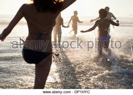 Freunde spielen in Wellen am Strand - Stockfoto