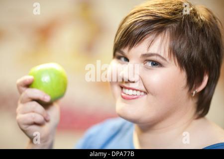 Porträt der jungen Frau hält Apfel hautnah - Stockfoto