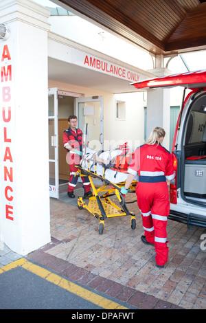 Sanitäter, die Patienten durch Krankenhaus Tür verschieben - Stockfoto